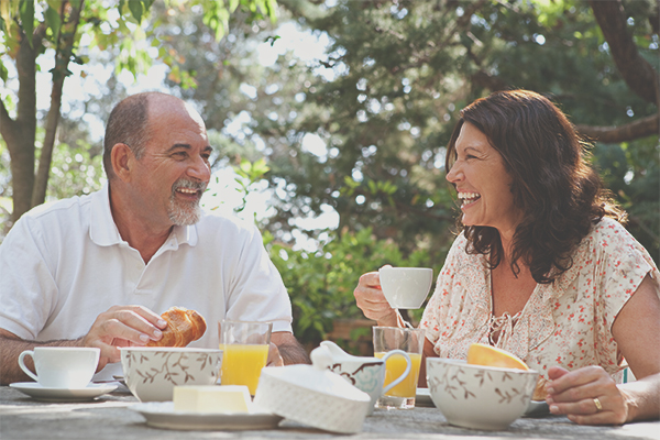 Older couple smiling while enjoying coffee, juice, and croissants at a table outside with trees in the background