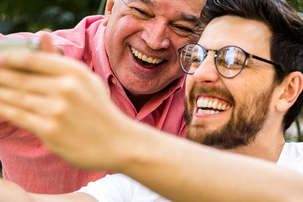 Young man with glasses and beard taking a selfie of him and older man in pink shirt smiling.