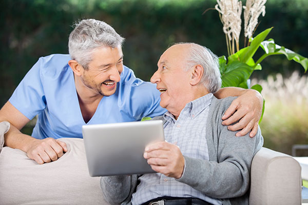Older man with Ipad in his hands looking and smiling at the dentist who has his arm around his shoulder