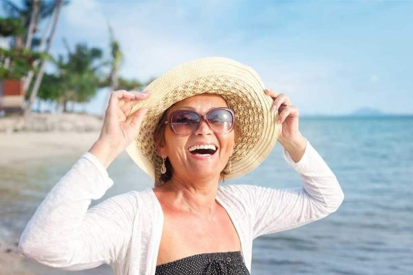 Smiling woman at beach with dark glasses on and straw hat, wearing white long-sleeved cover over black/white polka-dotted top