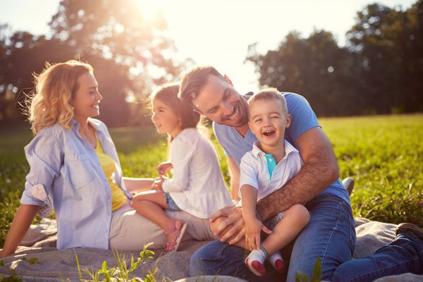 Young children sitting on laps of parents, all smiling, in outdoor field on a picnic.